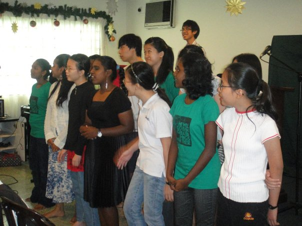 Girls from Shelter Home giving an item during Christmas service